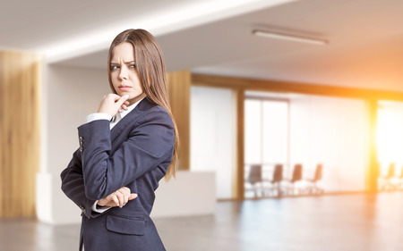 Portrait of a businesswoman in a suit. She is standing in an office with conference room and thinking with her fingers on the chin. 3d rendering. Mock up. Toned image.