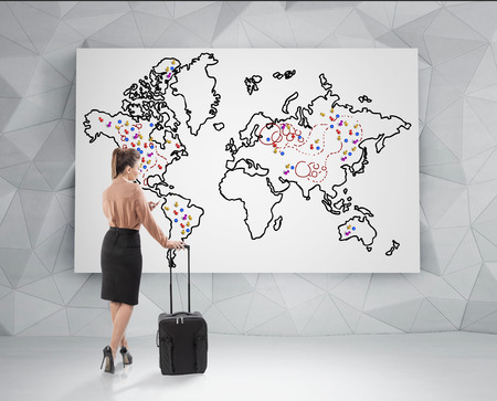 arrière plan noir et blanc: Rear view of a blond businesswoman with a black suitcase standing and looking at a world map with placemarks on it. Concept of travelling. Banque d'images