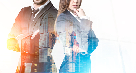 Close up of a bearded businessman and a pensive businesswoman standing near a large skyscraper panorama in the morning. Toned image. Mock up. Double exposure