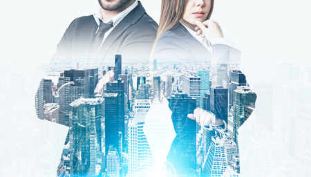 Close up of a bearded businessman and a pensive woman standing near a large skyscraper panorama in the morning. Toned image. Mock up. Double exposure Banque d'images