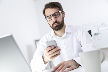 centered: Close up of a young bearded gentleman wearing a white shirt and glasses. He is sitting at his desk and looking at his smart phone screen.