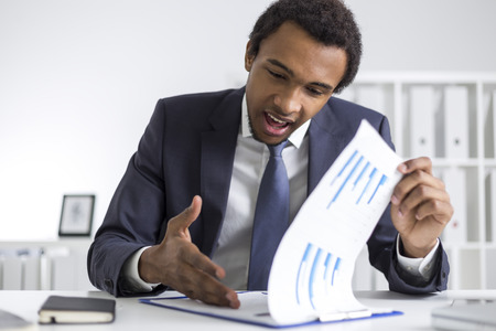 centered: Portrait of a young African American head of department in his company who is explaining the numbers to a person off camera