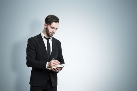 face centered: Bearded businessman in a suit is standing near a blue wall and writing in his notebook. Mock up