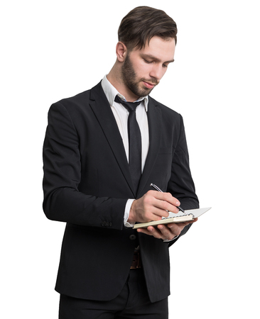 Isolated portrait of a bearded businessman writing in his small notebook while standing. He is wearing a black suit. Stock Photo