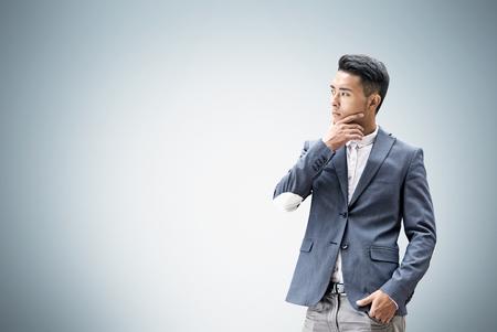 灰色の壁の近くに立って、考えては、アジア系のビジネスマンの肖像画。ビジネス意思決定の概念。モックアップします。