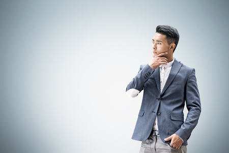 Portrait of an Asian businessman standing near a gray wall and thinking. Concept of business decision making. Mock up