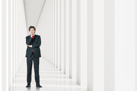 man looking out: Young businessman in a suit is standing in a white corridor and thinking. Concept of management. 3d rendering. Mock up