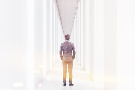 Rear view of a young businessman in a suit is standing in a white corridor and thinking. Concept of management. 3d rendering. Mock up. Toned image Stock Photo