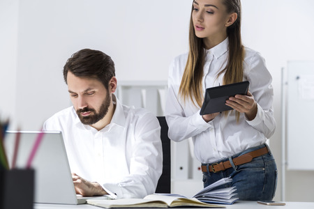 Close up of a bearded businessman and a woman with long hair standing beside him in office. She is holding her tablet and taking notes while looking at his laptop screen