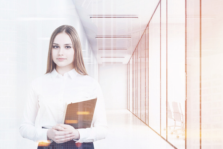 Young girl in an office suit is holding a black folder and standing in a white office corridor with conference rooms. 3d rendering. Mock up. Toned image. Double exposure Stock Photo