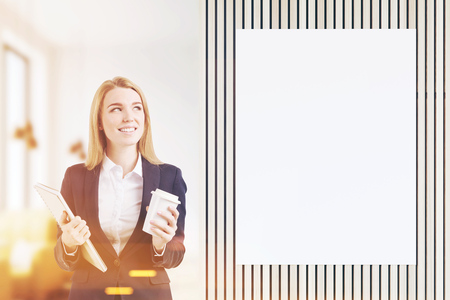 Beautiful blond woman with a cup of coffee and a notebook standing in a coffee shop near a blank poster. 3d rendering. Mock up. Toned image