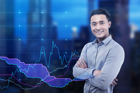 Cheerful Asian man portrait. He is standing with his arms crossed against a night cityscape with a blue graphs in the background. Mock up. Double exposure Stock fotó