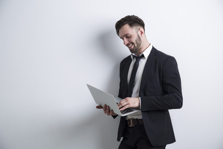 Portrait of a cheerful bearded young businessman standing near a white wall and working with his laptop. Mock up. Stock Photo