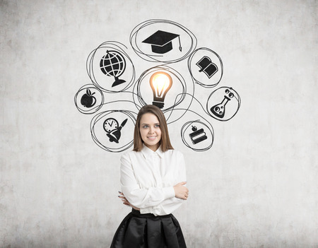 Portrait of a smiling blond woman standing with crossed arms near a concrete wall with study icons and a yellow light bulb drawn on it. Stock Photo