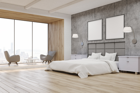 Side view of a bedroom interior with concrete walls, a large bed with two square posters hanging above it and two bedside tables. 3d rendering. Mock up.