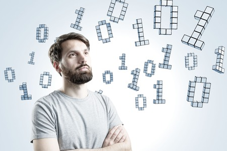 zeros: Portrait of a bearded businessman wearing a gray T-shirt and standing with crossed arms near a gray wall with zeros and ones flying around.