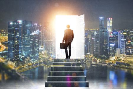 Pathway of opportunity. Back view of businessman exiting abstract night city room with stairs to enter open door with bright light. Success concept