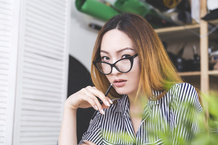 sultry: Close up portrait of sultry asian woman in stylish glasses holding pen near lips in office. Beautiful female posing at workplace