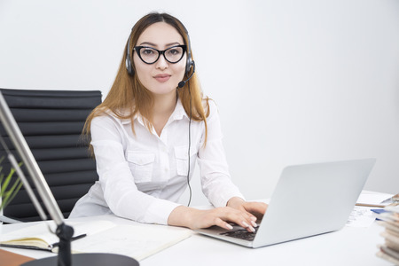 Attractive asian girl with headset using notebook at workplace. Call center operator dealing with clients in office