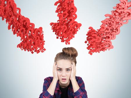Portrait eines jugendlich Mädchens gestresst in der Nähe einer grauen Wand sitzen. Es gibt rote Pfeile aus Fragezeichen auf sie zeigen. Standard-Bild - 70385031