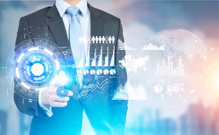 ぼやけた街背景の新しいハイテク ビジネス パネルを指してビジネスマン。仮想化技術の概念