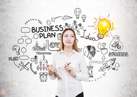 Pretty asian businesswoman with document on concrete background with business sketch. She is creating a business plan. Success concept Stock Photo