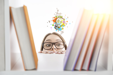 Short curious white girl trying to see what books there are on a library shelf. She wants to find new creative ideas. Filtered image