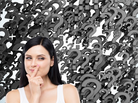 Portrait of a cunning woman in a tank top against black question marks background. Concept of multiple questions that need to be answered. Stock Photo