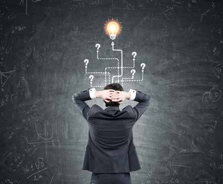 leading light: Rear view of a businessman wearing a suit and standing with his arms behind his head. He is looking at arrows leading to question marks and a light bulb sketch on a blackboard. Stock Photo