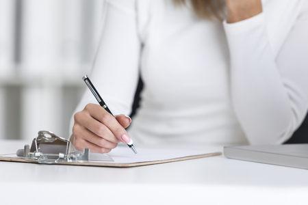 Close up of a woman?s hand holding a pen and going to write in her clipboard lying on a white desk in an office.