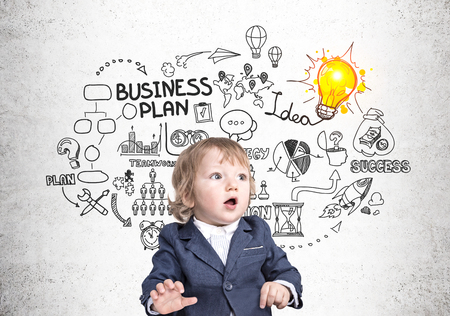 Prodigy: Portrait of a cute little boy in a suit sitting near a concrete wall with a business plan sketch and a glowing light bulb. Concept of business prodigy.