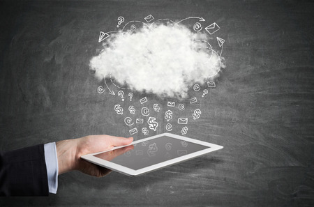 Close up of a businessman's hand holding a tablet computer under a cloud with icons raining from it. Blackboard. Stock Photo
