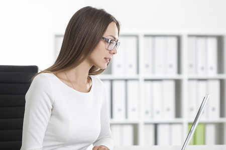 Side view of a girl in white clothes near her laptop in office. She is reading from the screen. Concept of office routine. Stock Photo