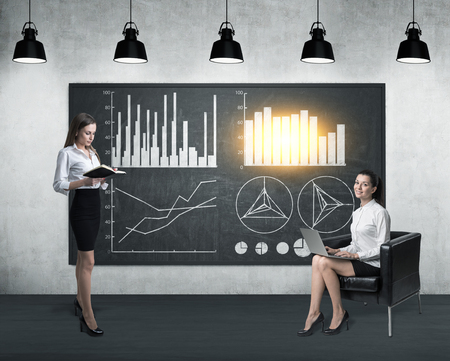 statistician: Two businesswoman near a blackboard with four graphs. One is sitting in an armchair with a laptop, the second is reading a book. Toned image Stock Photo