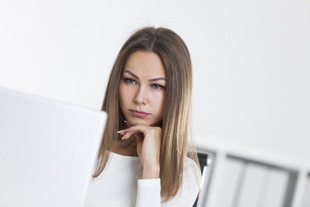 Close up of a sad woman in a white office is looking at her laptop screen. Bookshelves are seen in the background. Concept of not being satisfied with your work.