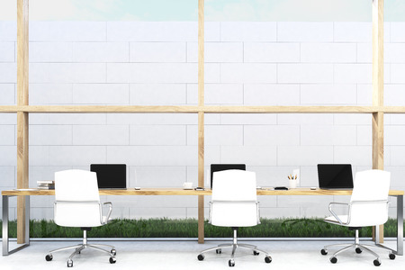 lawn chair: Front view of long office table standing near a white brick wall on grass. There are three laptops on the desk and white chairs. Wooden pillars. Sky is seen through ceiling. 3d rendering. Mock up