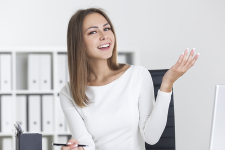 gesticulation: Happy blond woman in white clothes is sitting at her workplace and talking to someone off screen with gesticulation.