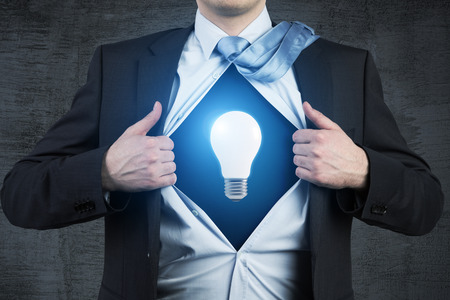 t bulb: Close up of a businessman tearing his shirt to demonstrate a light bulb glowing blue. Concept of a business idea.