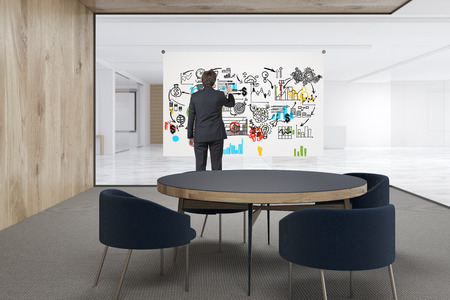glass office: Rear view of a man drawing a poster in an office with white and wooden walls. Waiting area with a round table surrounded by armchairs. 3d rendering. Mock up. Stock Photo