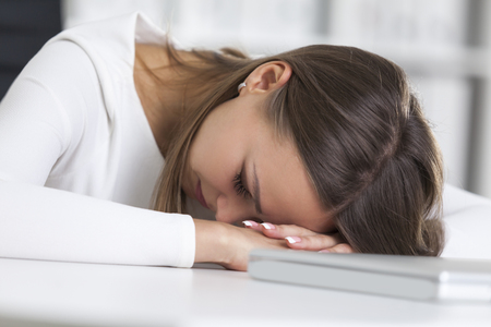 technolgy: Close up of a tired woman wearing white clothes and sleeping near her laptop in an office with white and green binders.