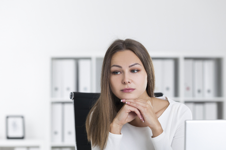 Portrait of a melancholic blond woman in a white office. She is sitting with her chin on her hands and looking the distance.