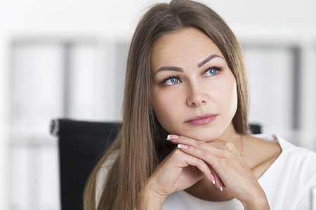 Close up of a dreamy blond woman in a white office. She is sitting with her chin on her hands and looking into distance. Stock Photo