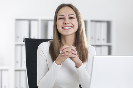 Portrait of a smiling blond businesswoman in white in her office. She is very cheerful and ready to work productively. Stock Photo