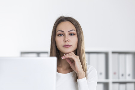 Pensive woman in a white office is looking at her laptop screen. Bookshelves are seen in the background. Concept of management.