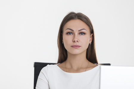 Close up of a serious girl in a white office. She is sitting at a desk against a white background. There is a laptop on her table. Stock Photo