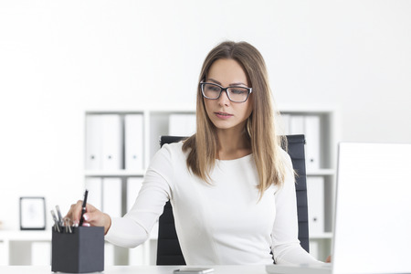 Portrait of a blond woman wearing glasses and sitting at her workplace in a white office taking a pen from a box.