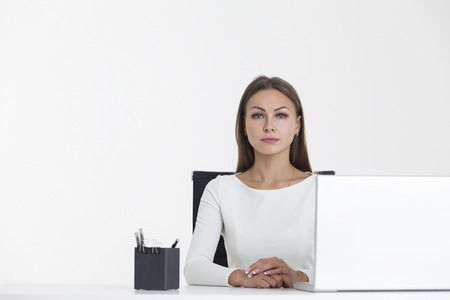 Portrait of a serious girl in a white office. She is sitting at a desk against a white background. There is a laptop on her table. Mock up.