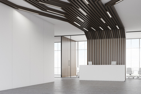 Corner of a room with a reception counter with two laptops. There is a meeting room with glass walls behind it. Black pipes are lowering from the ceiling. 3d rendering. Mock up. Stock Photo