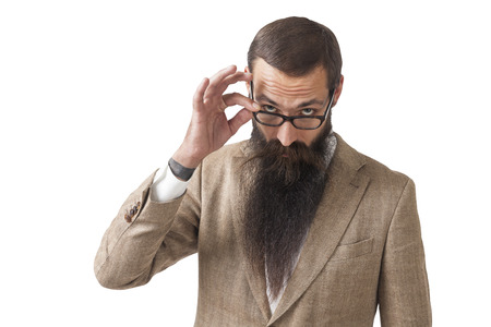 Isolated portrait of a businessman with a long beard wearing glasses and a beige suit and looking skeptically at someone off camera. Stock Photo