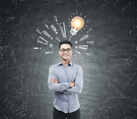 Asian businessman with crossed arms wearing glasses is standing near a blackboard with a light bulb and exclamation marks on it. Stock Photo
